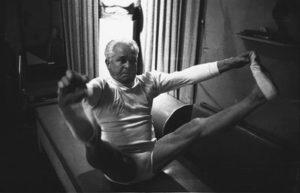 Joseph Hubertus Pilates qui tient ses pieds jambes tendues et en l'air