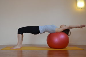 Femme en posture de Pilates, les épaules sur un gros ballon et bras en arrière. cours de Pilates sur Grenoble - Europole, Fontaine, Seyssinet